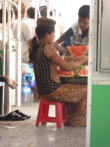 Selling watermelon on the train -- the tray goes on her head as she walks from carriage to carriage